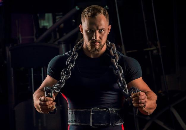 Atleta bonito com uma corrente em volta do pescoço está na academia e olha para a frente