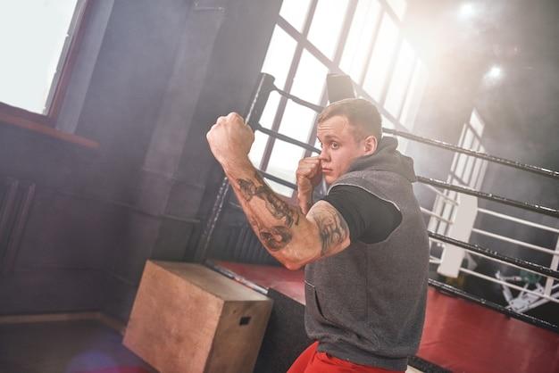 Atleta bonito confiante em roupas esportivas, jogando o uppercut. jovem boxeando com sombra em frente ao ringue de boxe colorido