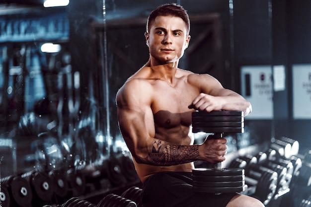 Atleta bonito jovem adulto malhando na academia, sentado num banco e segurando halteres com braços erguidos. interno, olhando o peso