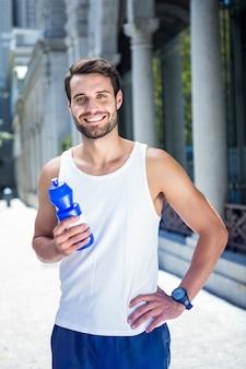 Atleta bonito sorridente segurando a garrafa