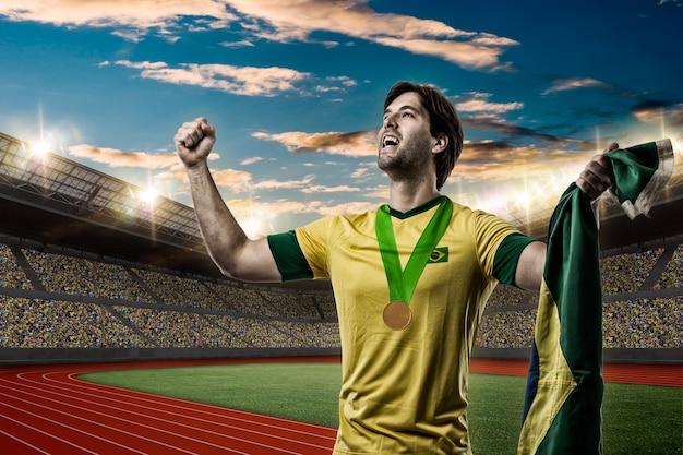 Atleta brasileiro conquistando medalha de ouro em estádio de atletismo.