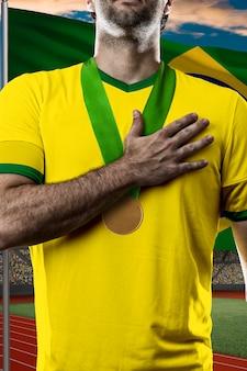 Atleta brasileiro conquistando medalha de ouro em frente a bandeira brasileira.
