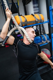 Atleta brincando no ginásio. tentando se pendurar na corda. conceito de piada.
