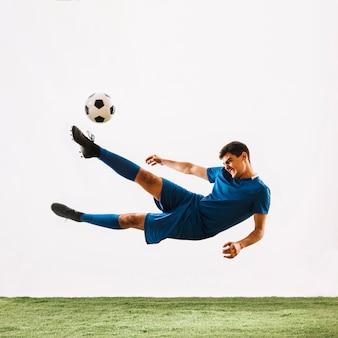 Atleta caindo e chutando a bola