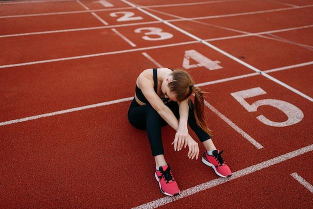 Atleta cansada sentada no chão, estádio