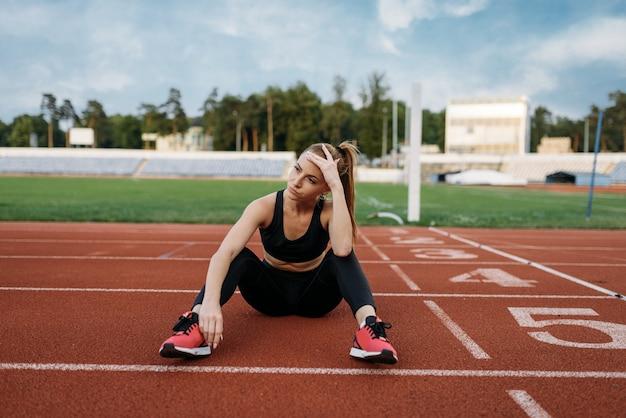Atleta cansada sentada no chão, treinando no estádio. mulher fazendo exercícios de alongamento antes de correr na arena ao ar livre