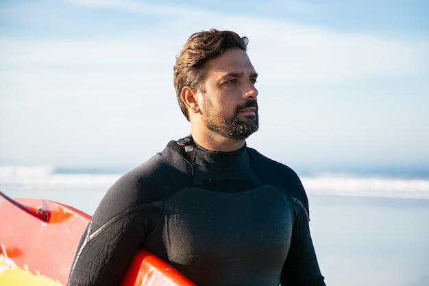 Atleta caucasiana com roupa de neoprene segurando a prancha de surf e olhando para longe
