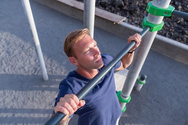 Atleta caucasiana faz pull ups com uma barra em um ginásio ao ar livre, jovem atraente treinando no verão, vestindo roupas esportivas. conceito de ginásio e fitness.