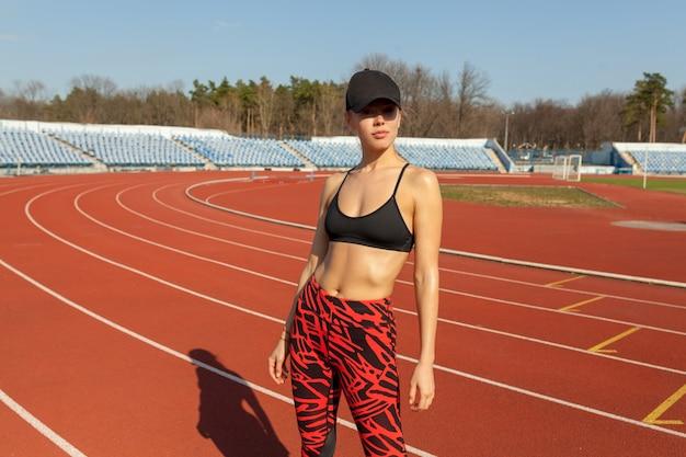 Atleta caucasiano linda garota descansando depois de correr em uma pista de corrida.
