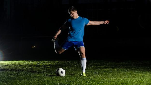 Atleta, chutando a bola de futebol