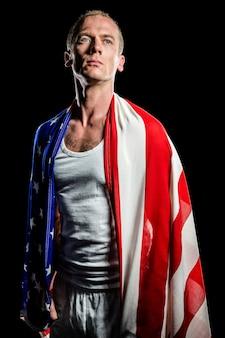 Atleta com bandeira americana enrolada em seu corpo