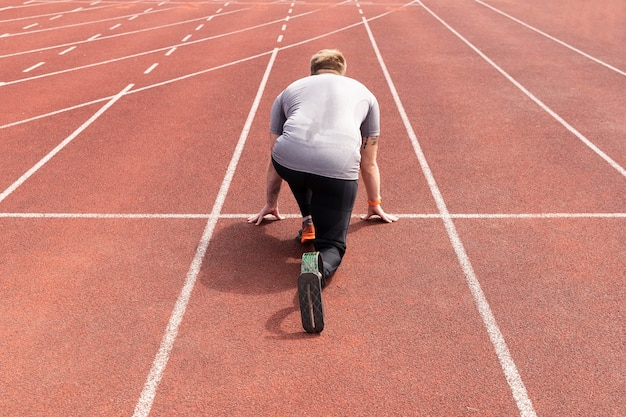 Atleta com deficiência de tiro completo pronto para correr