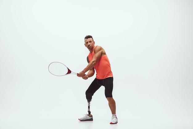 Atleta com deficiência em fundo branco, jogador de tênis