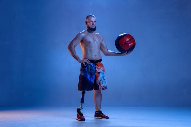 Atleta com deficiência ou amputado isolado na parede azul do estúdio