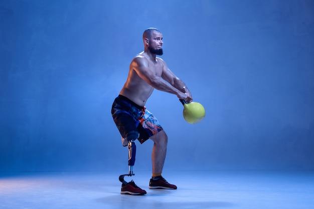 Atleta com deficiência ou amputado isolado na parede azul. esportista profissional masculino com treinamento de prótese de perna com pesos em neon. esporte para deficientes físicos e superação, conceito de bem-estar.