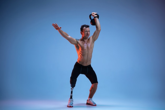 Atleta com deficiência ou amputado isolado no fundo azul do estúdio. esportista profissional masculino com treinamento de prótese de perna com pesos em neon.