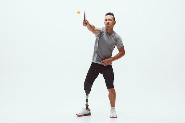 Atleta com deficiência ou amputado isolado no fundo branco do estúdio. jogador profissional de tênis de mesa masculino com treinamento de prótese de perna em estúdio. esporte para deficientes físicos e conceito de estilo de vida saudável.
