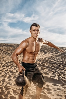 Atleta com kettlebell no deserto, voando na areia