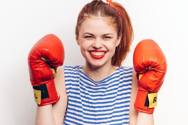 Atleta com luvas de boxe vermelhas em uma camiseta listrada de maquiagem brilhante de fundo claro