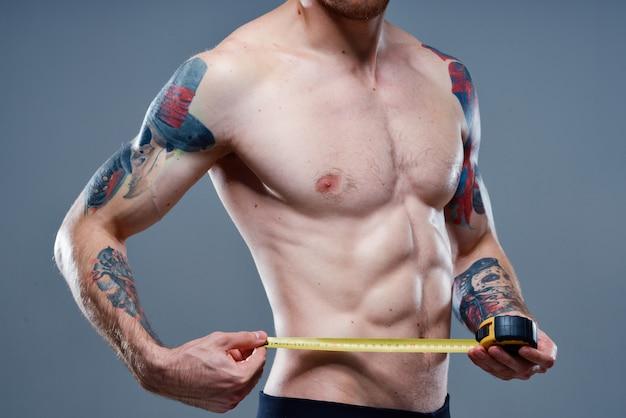 Atleta com músculos do braço aumentados e tatuagens fisiculturista fita centimétrica de fitness