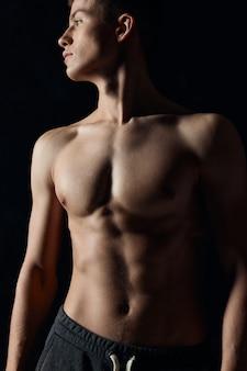 Atleta com o torso nu olhando para o lado em um plano de fundo preto vista recortada