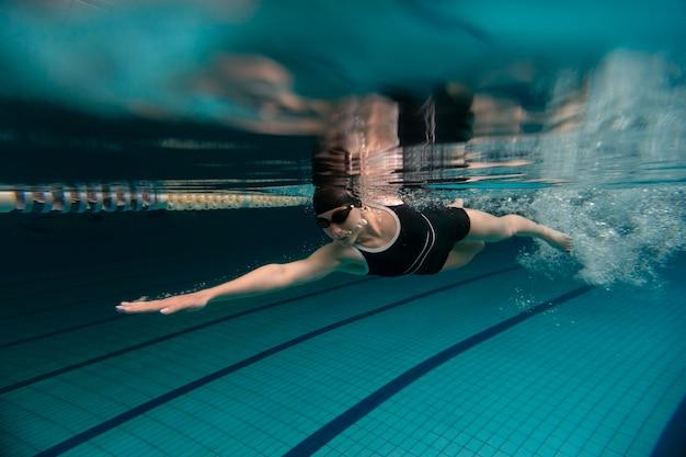 Atleta com óculos de natação tiro completo