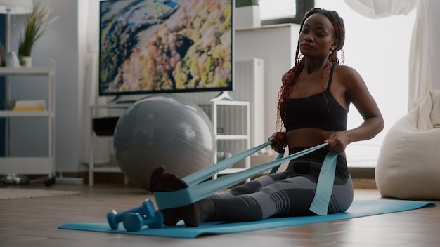 Atleta com pele negra em roupas esportivas, exercitando os músculos do corpo usando elástico de fitness, aproveitando o estilo de vida saudável sentado no mapa de ioga na sala de estar. mulher apta trabalhando no aquecimento do bem-estar antes do treino