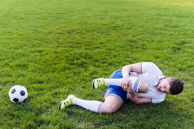 Atleta com perna machucada deitada na grama