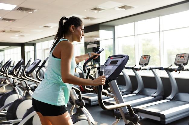 Atleta concentrada fazendo exercícios de crossfit na academia