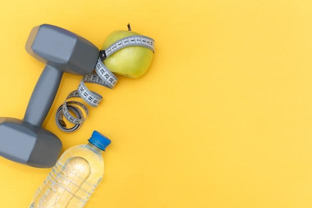 Atleta conjunto com roupas femininas, halteres e garrafa de água no fundo amarelo