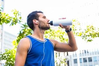 Atleta considerável beber fora da garrafa