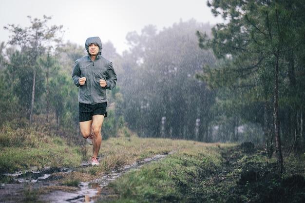 Atleta corredor na trilha de floresta de jaqueta esportiva cinza na chuva