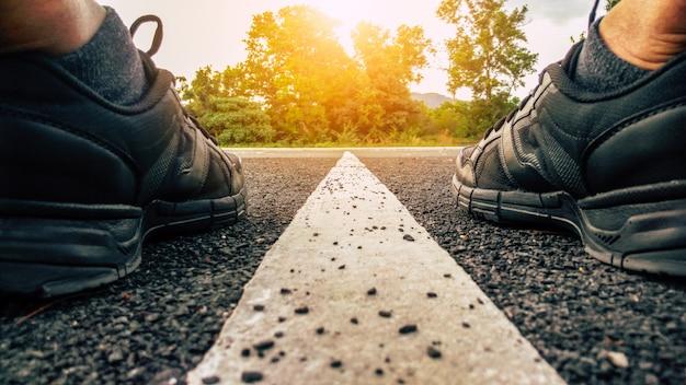 Atleta correndo pés de esporte na estrada de asfalto com linha branca reta e pôr do sol