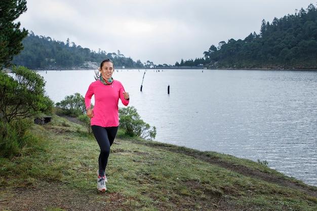 Atleta corriendo al aire libre cerca de un lago con montanas al fondo