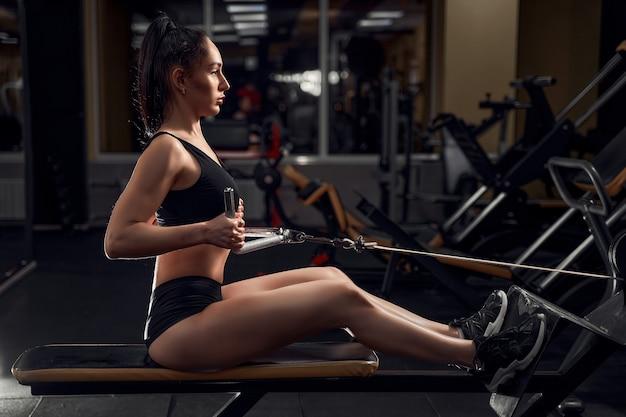 Atleta de aptidão muscular mulher fazendo exercícios pesados para as costas na máquina com cabo na academia