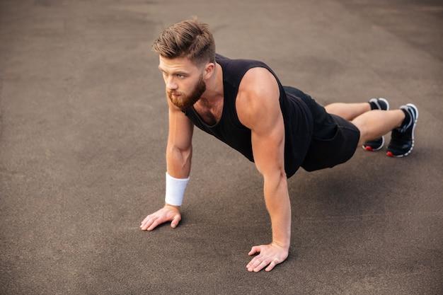 Atleta de barbudo jovem e bonito treinando e fazendo exercícios de prancha ao ar livre