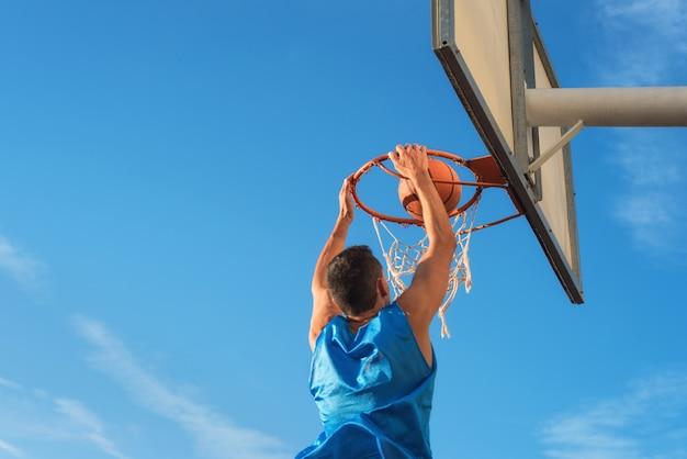 Atleta de basquete de rua, realizando slam dunk na quadra