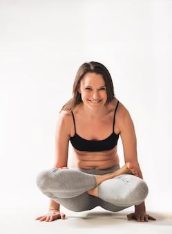 Atleta de bela jovem caucasiana concentrada fazendo asana yoga complexas em pé no chão sobre um fundo branco