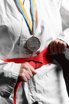 Atleta de caratê com faixa vermelha e close da medalha