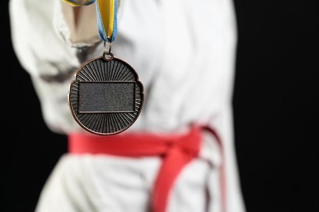 Atleta de caratê com faixa vermelha e medalha