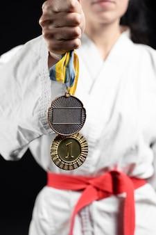 Atleta de caratê com faixa vermelha e medalhas