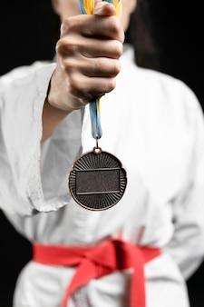 Atleta de caratê segurando medalha