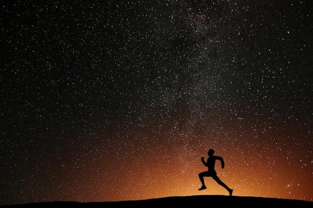 Atleta de corredor correndo na colina com fundo de bela noite estrelada. silhueta de treino de corrida de homem em tempo escuro, conceito de bem-estar.