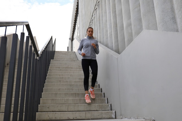 Atleta de corredor correndo nas escadas. aptidão da mulher é correr ao ar livre.