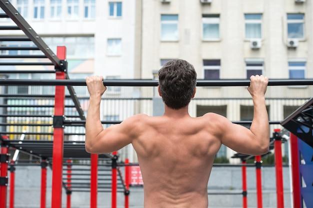 Atleta de costas musculosas de homem fazendo pull ups com forma adequada, o conceito de esporte.