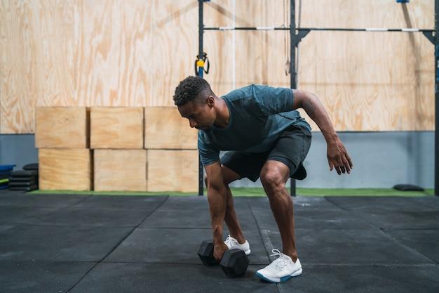 Atleta de crossfit fazendo exercício com halteres.