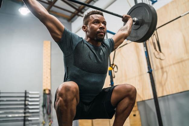 Atleta de crossfit fazendo exercício com um barbell.