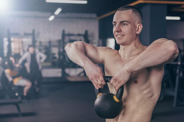 Atleta de crossfit muscular malhando com kettlebell