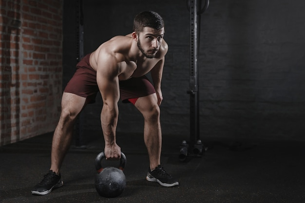 Atleta de crossfit se exercitando com um kettlebell na academia