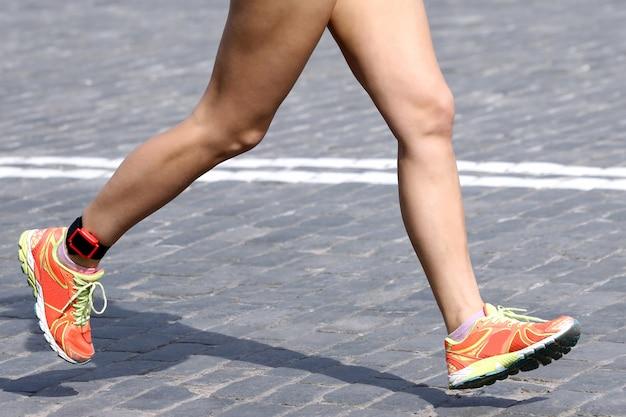 Atleta de distância correndo pés no pavimento de pedra. esporte e vitória